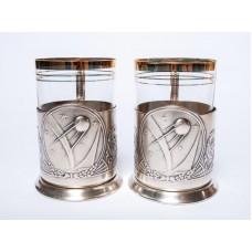 2 gab. Melhiora glāžu turētāji ar stikla glāzēm, Pirmais pavadonis